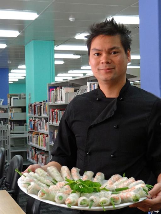Vu Do holding a plate of rice paper rolls